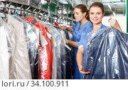 Купить «Confident woman worker of dry cleaner showing clean clothes in plastic garment bag», фото № 34100911, снято 9 мая 2018 г. (c) Яков Филимонов / Фотобанк Лори