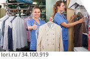 Купить «Two workers showing clean clothing», фото № 34100919, снято 9 мая 2018 г. (c) Яков Филимонов / Фотобанк Лори