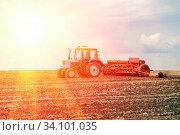 Купить «Russia Samara May 2020: Spring. Sowing work. A tractor with a seeder trailer works in the field at sunset.», фото № 34101035, снято 11 мая 2020 г. (c) Акиньшин Владимир / Фотобанк Лори