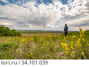 Купить «A mature man stands on a hill and enjoys a picturesque view of the steppe valley.», фото № 34101039, снято 11 мая 2020 г. (c) Акиньшин Владимир / Фотобанк Лори