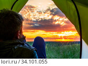 A mature man peeks out of a tourist tent and admires the picturesque sunset of the day. Стоковое фото, фотограф Акиньшин Владимир / Фотобанк Лори