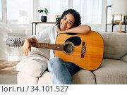 Купить «Happy woman with guitar sitting on sofa at home», фото № 34101527, снято 20 июня 2020 г. (c) Tryapitsyn Sergiy / Фотобанк Лори