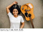 Купить «Woman with guitar and headphones lying on floor», фото № 34101535, снято 20 июня 2020 г. (c) Tryapitsyn Sergiy / Фотобанк Лори