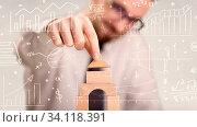 Купить «Young handsome businessman using wooden building blocks with white calculations scribbled around him», фото № 34118391, снято 7 августа 2020 г. (c) easy Fotostock / Фотобанк Лори