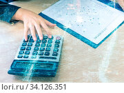 Double exposure of businesswoman hand with calculator and New york skyline building background. Стоковое фото, фотограф Zoonar.com/Vichaya Kiatying-Angsulee / easy Fotostock / Фотобанк Лори
