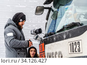 Купить «Orenburg, Russia - December, 17, 2019: A videographer sets up a video camera in front of the windshield of a truck cab», фото № 34126427, снято 17 декабря 2019 г. (c) Вадим Орлов / Фотобанк Лори