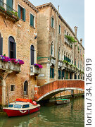 Купить «Venetian canal with bridge and moored motorboat», фото № 34126919, снято 18 июня 2018 г. (c) Роман Сигаев / Фотобанк Лори