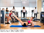 Young woman in sport wear doing sport in gym. Стоковое фото, фотограф Zoonar.com/Kotin Dmitrii / age Fotostock / Фотобанк Лори