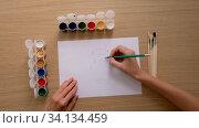 Crop unrecognizable artist drawing with pencil on paper at work. Стоковое видео, видеограф Ekaterina Demidova / Фотобанк Лори