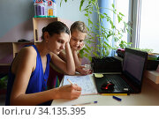 tutor explains to the child how to do the job in a notebook. Стоковое фото, фотограф Иванов Алексей / Фотобанк Лори