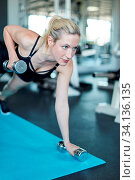 Junge Frau trainiert Trizeps Muskel beim Kurzhantel Workout im Fitnesscenter. Стоковое фото, фотограф Zoonar.com/Robert Kneschke / age Fotostock / Фотобанк Лори