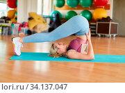 Junge Frau dehnt Rücken und Beine im Nackenstand beim Yoga im Fitnesscenter. Стоковое фото, фотограф Zoonar.com/Robert Kneschke / age Fotostock / Фотобанк Лори
