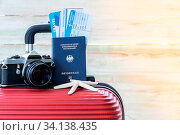 Купить «Red luggage with camera passport air ticket ans starfish for Summer background against blue wooden wall background with copy space ans warm sunlight», фото № 34138435, снято 3 июля 2020 г. (c) easy Fotostock / Фотобанк Лори