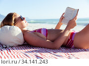 Woman reading a book while laying on the beach. Стоковое фото, агентство Wavebreak Media / Фотобанк Лори