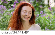 Portrait of a redhead young adult woman among flowers in a city park on a sunny summer day. Стоковое видео, видеограф Алексей Кузнецов / Фотобанк Лори