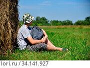 Купить «Teenager with a backpack sitting next to a stack of straw», фото № 34141927, снято 3 июля 2020 г. (c) age Fotostock / Фотобанк Лори