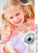 Kleines Mädchen beim Zahnarzt spült den Mund mit einem Becher Wasser aus zur Mundhygiene. Стоковое фото, фотограф Zoonar.com/Robert Kneschke / age Fotostock / Фотобанк Лори