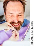 Купить «Mann als Patient bei der Auswahl der richtigen Zahnfarbe bei der Zahnaufhellung beim Zahnarzt», фото № 34142815, снято 3 июля 2020 г. (c) age Fotostock / Фотобанк Лори