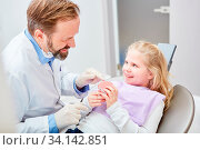 Zahnarzt zeigt Kind als Patient ein Gebiss Modell und erklärt die geplante Karies Behandlung. Стоковое фото, фотограф Zoonar.com/Robert Kneschke / age Fotostock / Фотобанк Лори