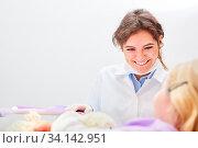 Freundliche Zahnärztin oder Arzthelferin und ein Kind als Patient im Gespräch bei der Behandlung. Стоковое фото, фотограф Zoonar.com/Robert Kneschke / age Fotostock / Фотобанк Лори