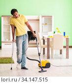 Купить «Injured man on crutches vacuum cleaning house», фото № 34147515, снято 30 мая 2018 г. (c) Elnur / Фотобанк Лори