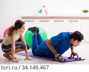Fitness instructor helping sportsman during exercise. Стоковое фото, фотограф Elnur / Фотобанк Лори