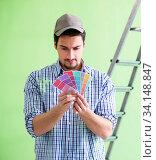 Купить «Young man contractor choosing color from rainbow», фото № 34148847, снято 2 мая 2018 г. (c) Elnur / Фотобанк Лори