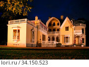 Купить «An old manor house (architectural eclecticism with elements of classics) in the home park at sunset twilight hours, antique house with high relief and portico. Late summer-early autumn», фото № 34150523, снято 7 июля 2020 г. (c) easy Fotostock / Фотобанк Лори
