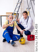 Young male doctor and old contractor in first aid concept. Стоковое фото, фотограф Elnur / Фотобанк Лори