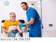 Old man visiting young male doctor. Стоковое фото, фотограф Elnur / Фотобанк Лори
