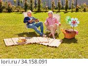 Senioren Paar als Rentner im Garten im Sommer entspannt sich bei einem Picknick. Стоковое фото, фотограф Zoonar.com/Robert Kneschke / age Fotostock / Фотобанк Лори