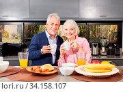 Glückliches Paar Senioren beim Frühstück mit einem Becher Kaffee in der Küche. Стоковое фото, фотограф Zoonar.com/Robert Kneschke / age Fotostock / Фотобанк Лори