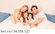 Glückliche Familie mit zwei Kindern beim Kuscheln im Bett als Header. Стоковое фото, фотограф Zoonar.com/Robert Kneschke / age Fotostock / Фотобанк Лори