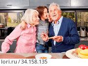 Junge als Enkelkind flüstert seinen Großeltern ein Geheimnis ins Ohr in der Küche. Стоковое фото, фотограф Zoonar.com/Robert Kneschke / age Fotostock / Фотобанк Лори