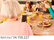 Familie beim Abendessen oder Mittagessen am Tisch mit Smartphone und Handy. Стоковое фото, фотограф Zoonar.com/Robert Kneschke / age Fotostock / Фотобанк Лори