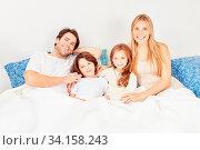 Glückliche Familie mit zwei Kindern liegt morgens zusammen im Bett. Стоковое фото, фотограф Zoonar.com/Robert Kneschke / age Fotostock / Фотобанк Лори