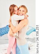 Tochter umarmt Mutter und gibt ihr liebevoll einen Kuss im Bett im Schlafzimmer. Стоковое фото, фотограф Zoonar.com/Robert Kneschke / age Fotostock / Фотобанк Лори