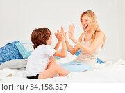Junge spielt zusammen mit seiner Mutter auf dem Bett ein fröhliches Klatschspiel. Стоковое фото, фотограф Zoonar.com/Robert Kneschke / age Fotostock / Фотобанк Лори
