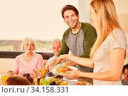 Glückliches Paar mit Großeltern am Esstisch beim Mittagessen oder Abendessen. Стоковое фото, фотограф Zoonar.com/Robert Kneschke / age Fotostock / Фотобанк Лори