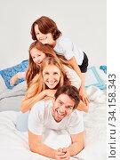 Glückliche Familie mit zwei Kindern liegt vergnügt zusammen im Bett im Schlafzimmer. Стоковое фото, фотограф Zoonar.com/Robert Kneschke / age Fotostock / Фотобанк Лори