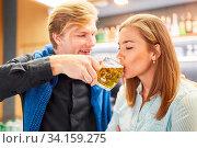 Junger Mann flösst seiner Freundin ein Glas Bier ein in einer Bar oder Kneipe. Стоковое фото, фотограф Zoonar.com/Robert Kneschke / age Fotostock / Фотобанк Лори