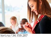 Junge Frau als Bedienung oder Aushilfe im Restaurant notiert Bestellung von Gast. Стоковое фото, фотограф Zoonar.com/Robert Kneschke / age Fotostock / Фотобанк Лори
