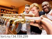 Drei Männer am Tresen in einer Kneipe beim Bier trinken als Männerabend. Стоковое фото, фотограф Zoonar.com/Robert Kneschke / age Fotostock / Фотобанк Лори