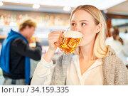 Junge Frau beim Bier trinken am Feierabend in einer Kneipe oder einem Pub. Стоковое фото, фотограф Zoonar.com/Robert Kneschke / age Fotostock / Фотобанк Лори