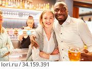 Multikulturelles Paar beim Dating in einer Kneipe oder Bar beim Bier trinken. Стоковое фото, фотограф Zoonar.com/Robert Kneschke / age Fotostock / Фотобанк Лори