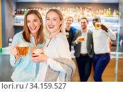 Zwei Freundinnen feiern ausgelassen mit Bier in einer Kneipe oder einem Pub. Стоковое фото, фотограф Zoonar.com/Robert Kneschke / age Fotostock / Фотобанк Лори