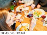 Junge Frau trinkt ein Glas Rotwein zum Abendessen im Restaurant mit Freunden. Стоковое фото, фотограф Zoonar.com/Robert Kneschke / age Fotostock / Фотобанк Лори