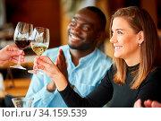 Junge Frau beim Anstoßen mit Wein als Gratulation zum Geburtstag im Bistro. Стоковое фото, фотограф Zoonar.com/Robert Kneschke / age Fotostock / Фотобанк Лори