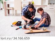 Купить «The young father repairing skateboard with his son at home», фото № 34166659, снято 11 июля 2020 г. (c) easy Fotostock / Фотобанк Лори