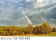 Купить «Colorful double Rainbow on cloudy sky over forest after spring rain - beautiful spring rural landscape. Celestial phenomenon - sunlight refraction in humid...», фото № 34169443, снято 11 июля 2020 г. (c) easy Fotostock / Фотобанк Лори